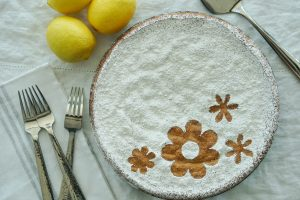 Spanish Almond Cake on white table cloth with napkin, forks and lemons