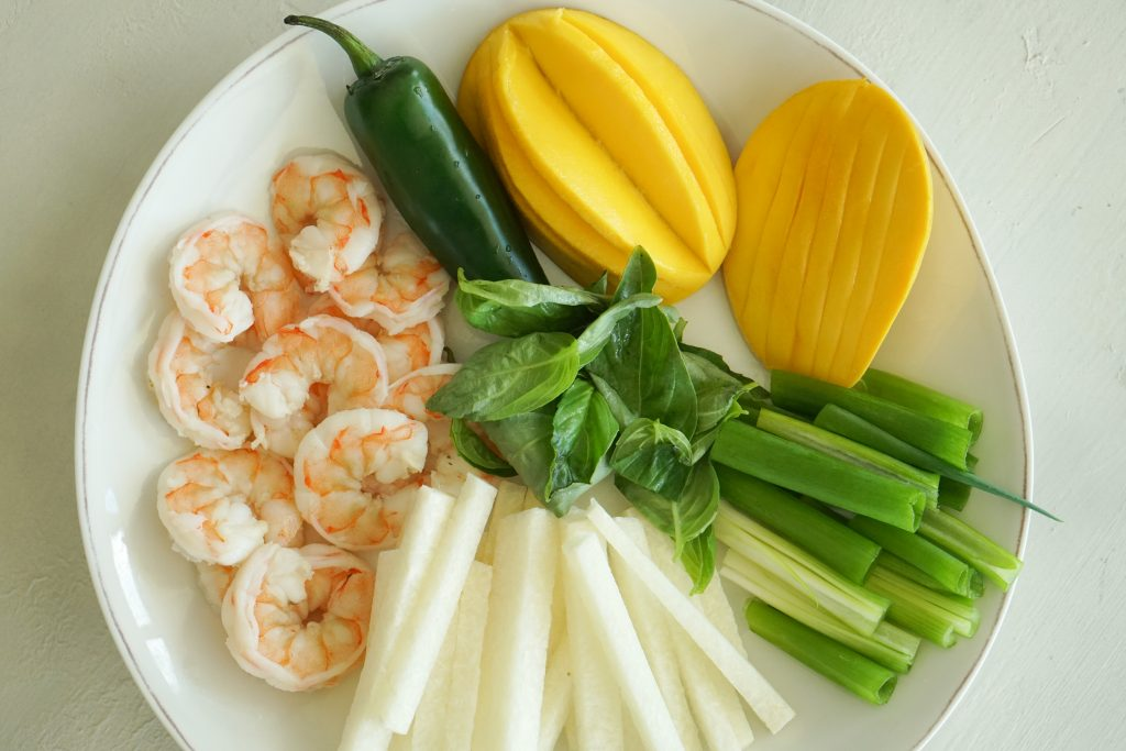 Shrimp jicama sticks scallions basil jalapeno and cut mango on a plate