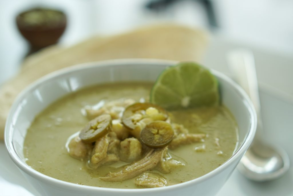 Slow Cooker Chicken Pozole in white bowl with lime round and a small wooden bowl of pepitas and stool in background