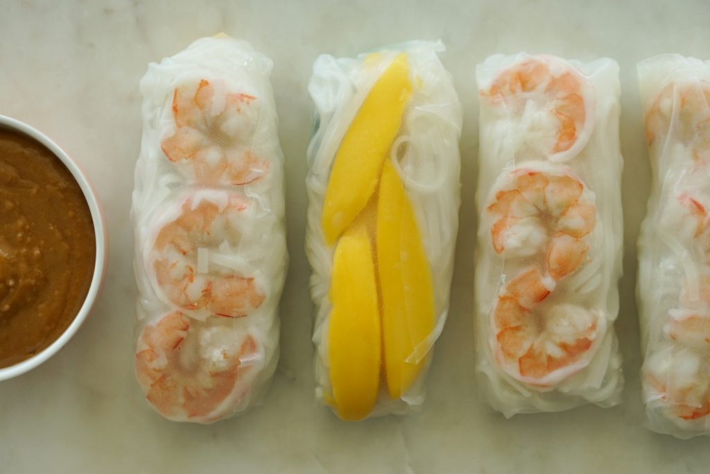 Mango & Shrimp Fresh Spring Rolls on platter with Peanut Dipping Sauce in a bowl