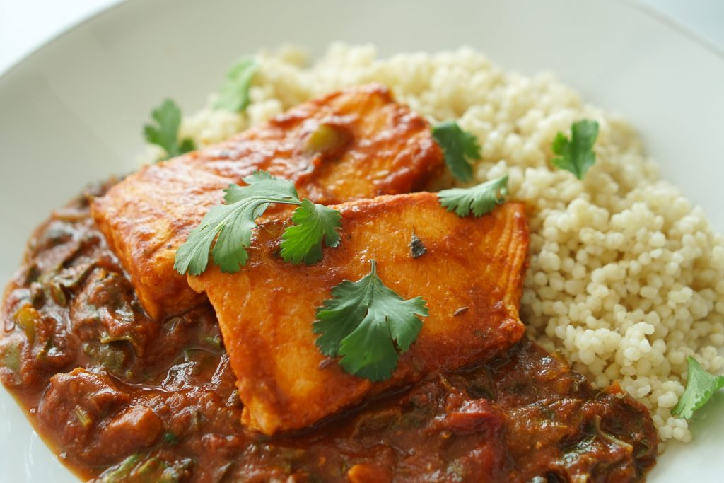 Smoky Braised Salmon & Swiss Chard on a plate with couscous
