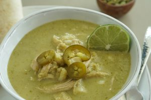 Slow Cooker Chicken Pozole in white bowl with lime round and a small wooden bowl of pepitas in background