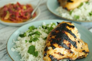 Grilled Caribbean Chicken & Coconut Rice on two plates with onion caper sauce in background