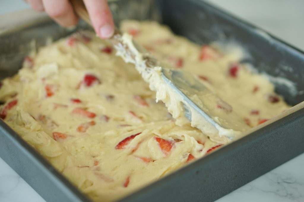 Strawberry Cake batter being smoothed with a spatula in a cake pan