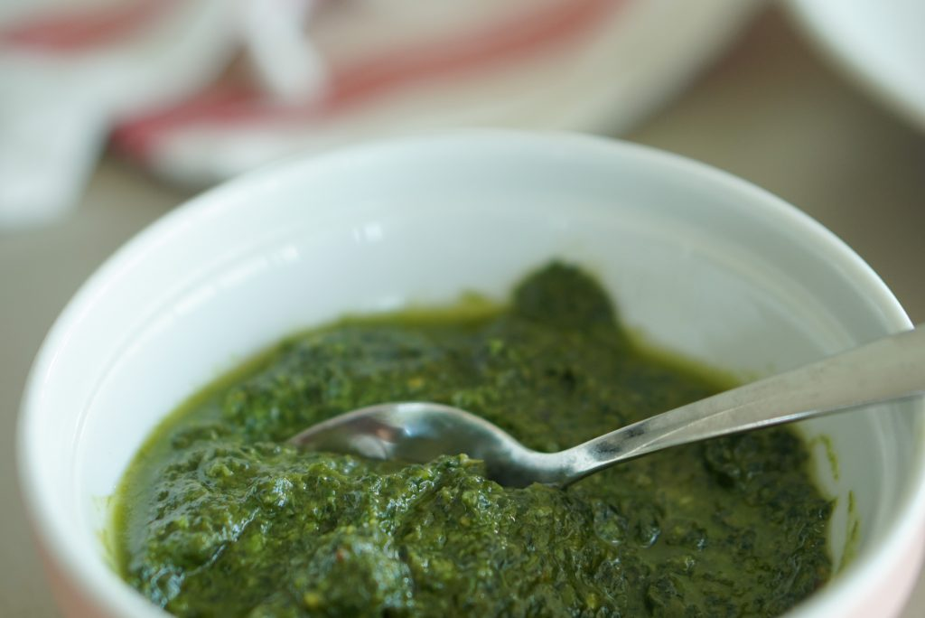 Basil pesto in a bowl with a spoon