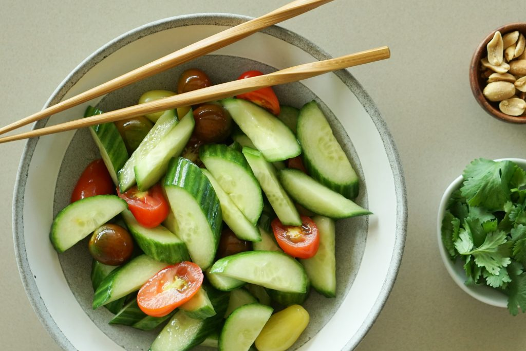 Asian Cucumber Salad in serving bowl with chopsticks, peanuts and cilantro on the side