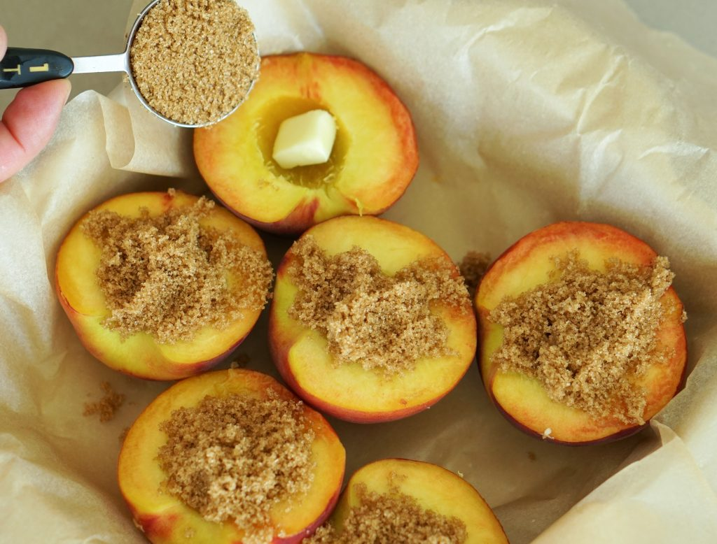 Peaches halved in a parchment lined baking dish with brown sugar and a pat of butter and ready for the oven