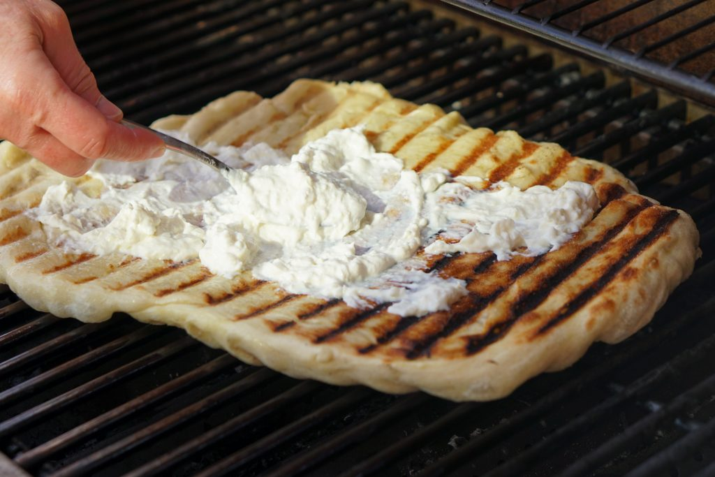 Pizza dough on grill grates flipped over so one side is nicely charred and spoon spreading ricotta