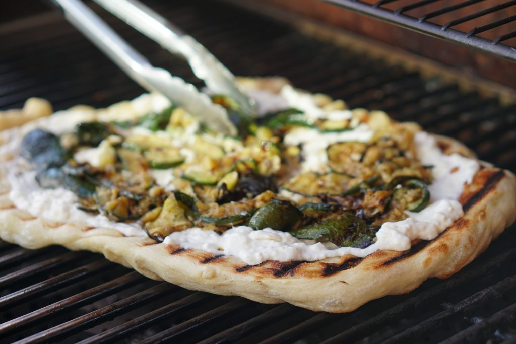 Grilled pizza topped with ricotta and zucchini being added with grill tongs