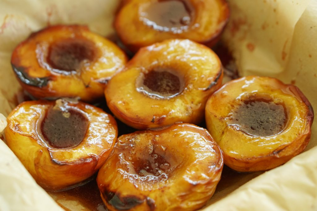Baked peaches that have been halved holding a melted butter and brown sugar mixture