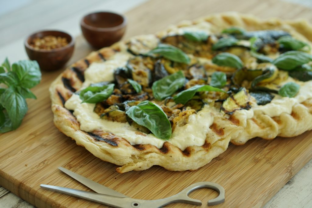 Grilled Zucchini Pizza with Ricotta & Feta on cutting board with pizza scissors