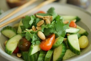 Close up of Asian Cucumber Salad in serving bowl with chopsticks