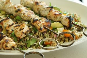 Yogurt Marinated Chicken Skewers with Avocado Apricot Quinoa Salad in a serving bowl