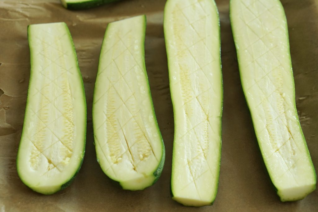 Zucchini on parchment cut in half lengthwise and scored in a diamond pattern