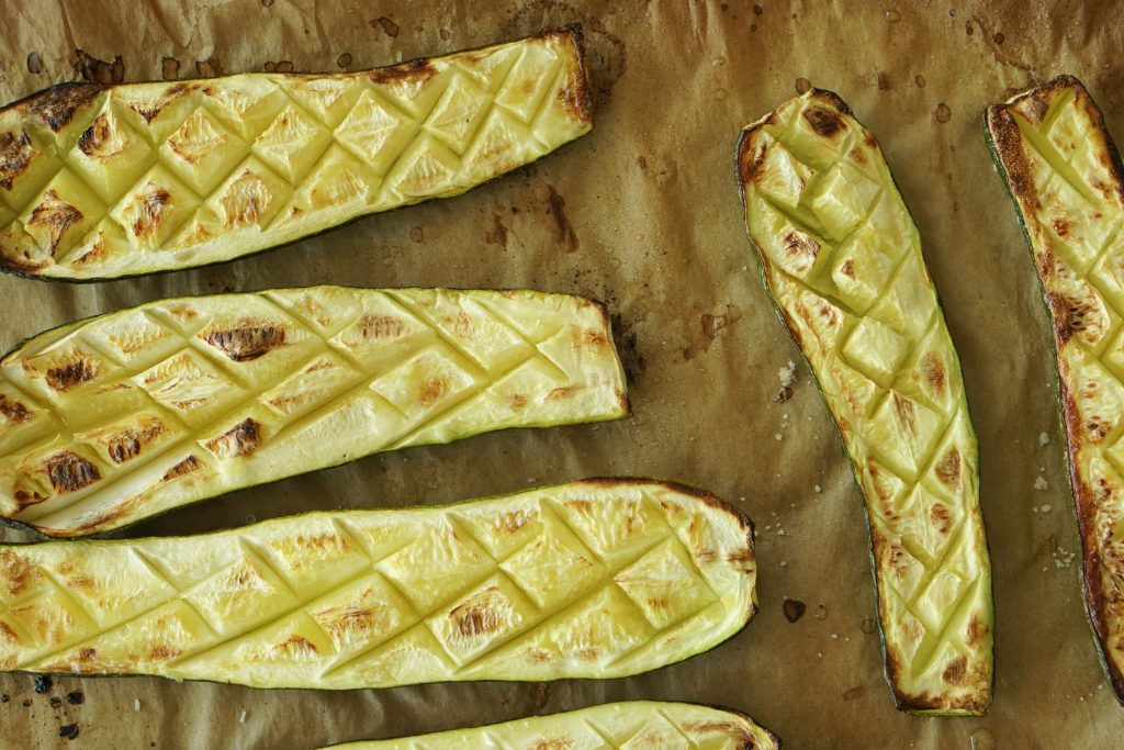 Roasted zucchini on parchment cut in half lengthwise and scored in a diamond pattern