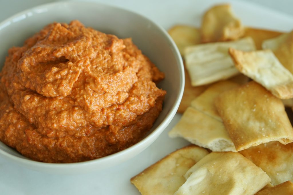 Charred Pepper & Walnut Dip in bowl with pita chips on side