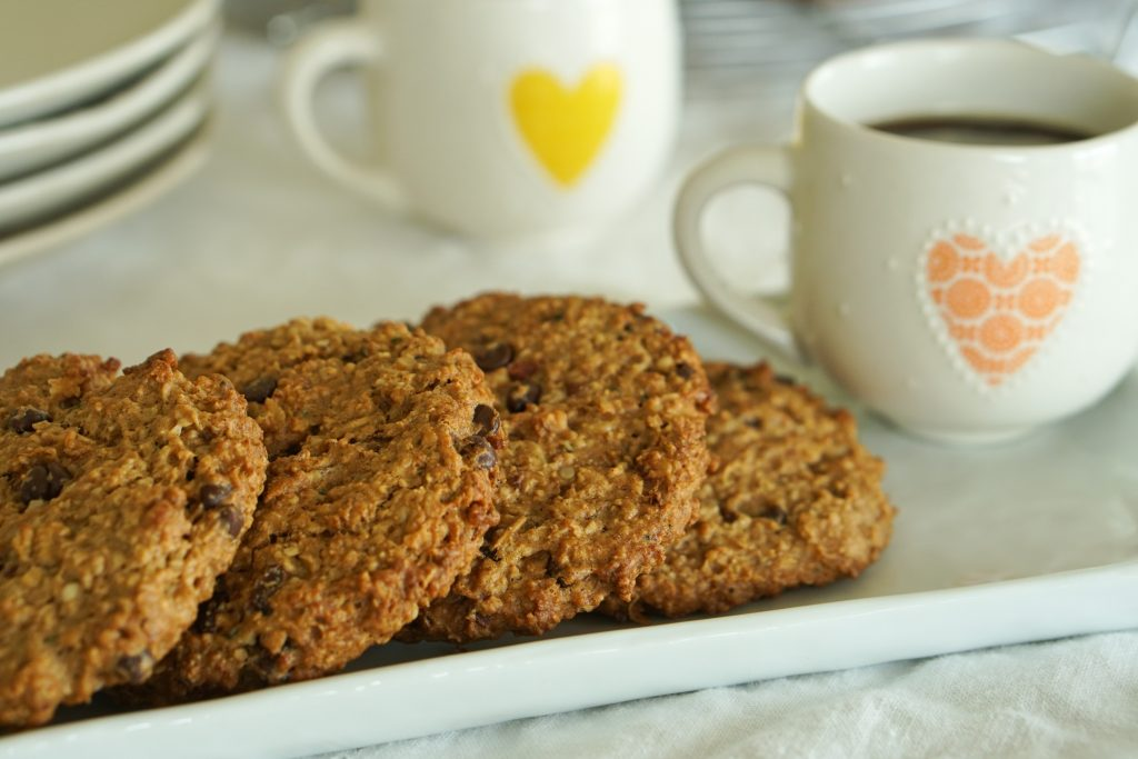 4 Oatmeal Chocolate Chip Breakfast Cookies on a small platter with a coffee mug with more cookies, mug and plates in background