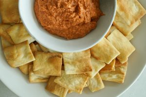 Top down of Charred Pepper & Walnut Dip in bowl with pita chips on side