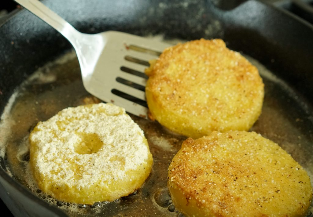 Frying breaded tomatoes in pan with metal spatula
