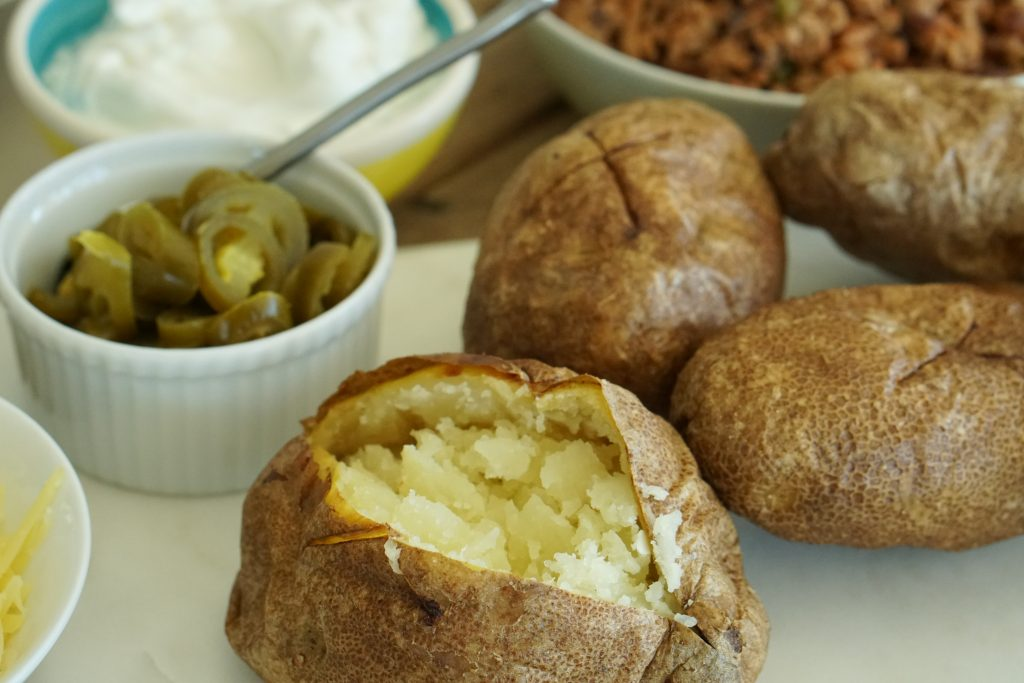 Jacket Potato cut open on white marble with DIY toppings in bowls