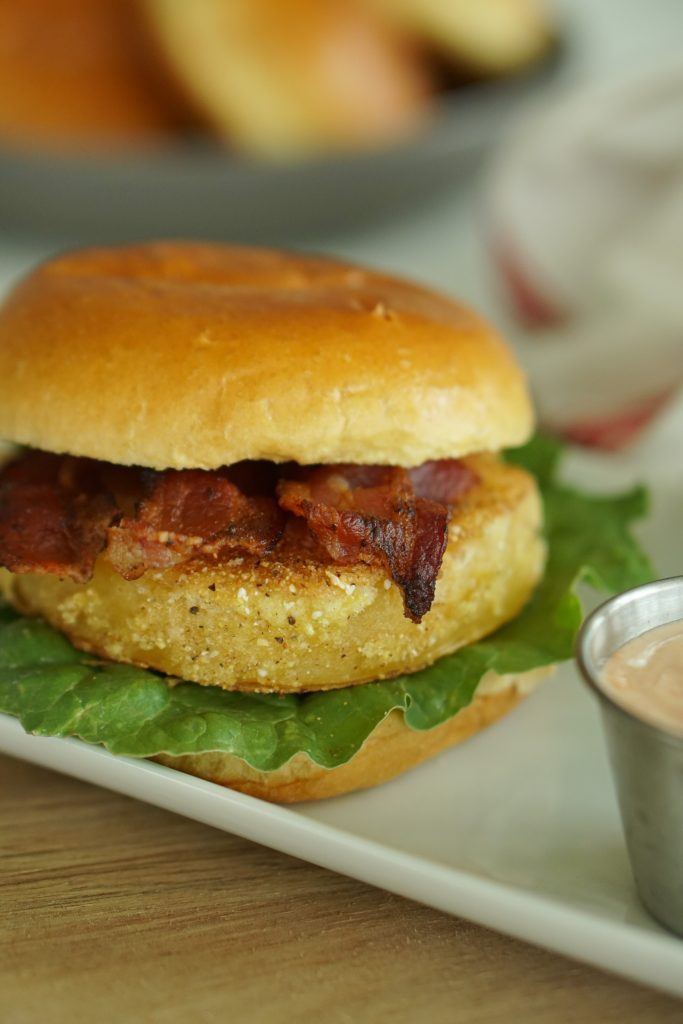 Fried Green Tomato BLT on plate with sriracha sauce in metal cup