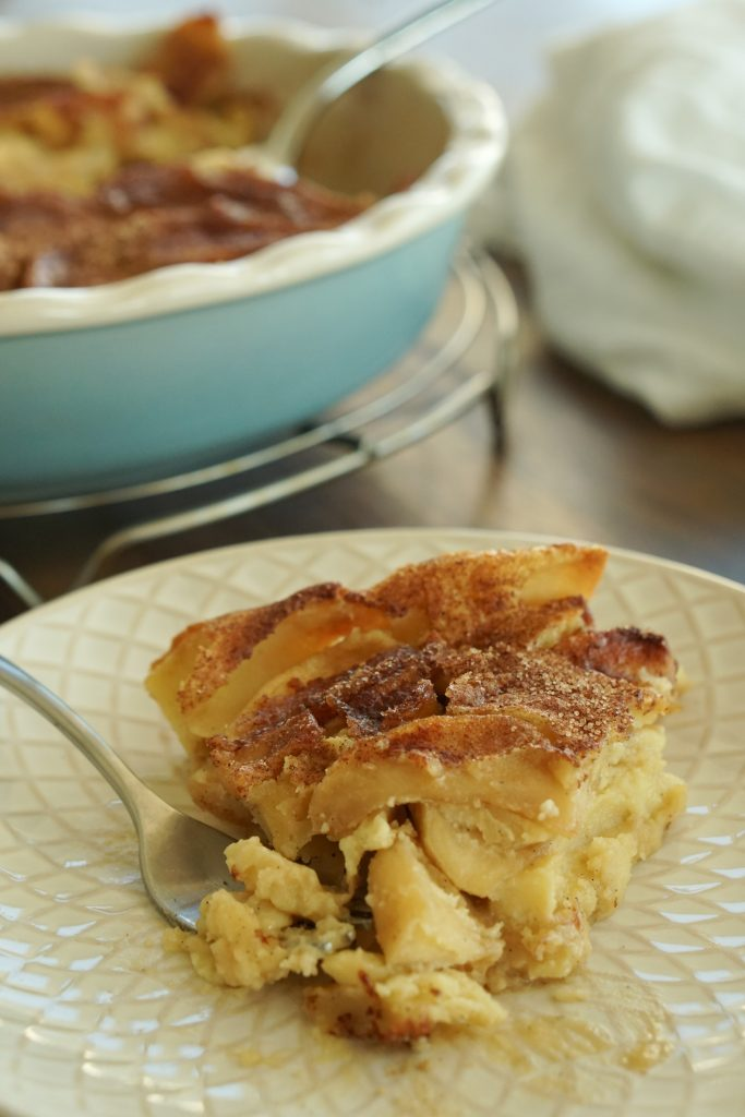 Piece of Caramelized Apple Custard Cake on plate with blue pie plate in background